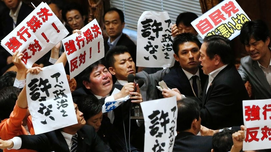 "Opposition lawmakers surround Yasukazu Hamada, right, chairman of the lower house special committee on security legislation, as Hamada continues the committee proceedings at the parliament in Tokyo, Wednesday, July 15, 2015.  The parliamentary committee has approved a package of highly controversial security legislation in a vote forced by Prime Minister Shinzo Abe's ruling bloc disrupted by opponents' massive protests.  The banners held by opposition lawmakers read  ""Oppose forcible passage (of the bills)"" and ""Never forgive Abe's politics."" (AP Photo/Shuji Kajiyama)"