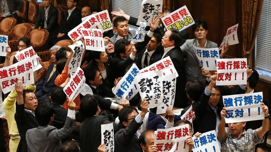 "Yasukazu Hamada, top right, the chairman of the lower house special committee on security legislation, is surrounded by opposition lawmakers as Hamada continues the committee proceedings against a group of opposition lawmakers, at the parliament in Tokyo, Wednesday, July 15, 2015.  The Japanese parliamentary committee has approved a package of highly controversial security legislation in a vote forced by Prime Minister Shinzo Abe's ruling bloc disrupted by opponents' massive protests.  The banners held by opposition lawmakers read  ""Oppose forcible passage (of the bills)"" and ""Never forgive Abe's politics."" (AP Photo/Shuji Kajiyama)"