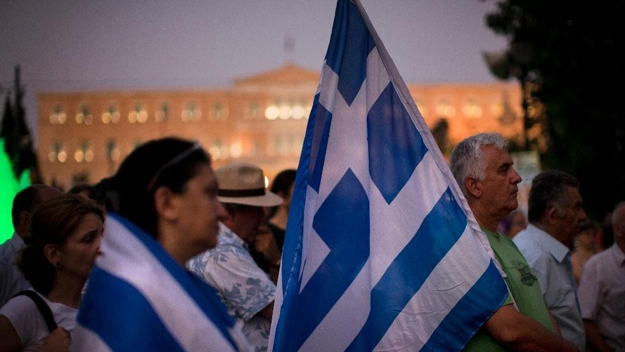 Pensioners wait for the opening of the national bank of Greece to withdraw a maximum of 120 euros ($134) for the week in central Athens, Wednesday, July 15, 2015. Greece's Parliament votes Wednesday on an 85-billion-euro bailout deal meant to prevent the country's economy from collapsing. (AP Photo/Emilio Morenatti)