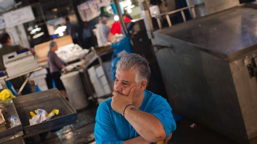 A shopkeeper waits for customers at a fishing market in central Athens, Wednesday, July 15, 2015. Greece's Parliament votes Wednesday on an 85-billion-euro bailout deal meant to prevent the country's economy from collapsing. (AP Photo/Emilio Morenatti)
