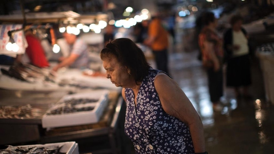 A woman looks at fish in a fishing market in central Athens, Wednesday, July 15, 2015. Greece's Parliament votes Wednesday on an 85-billion-euro bailout deal meant to prevent the country's economy from collapsing. (AP Photo/Emilio Morenatti)