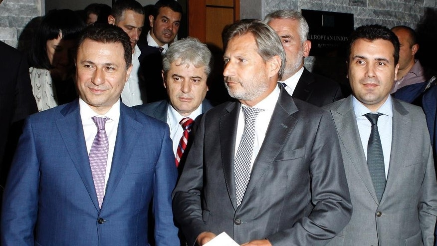 European Neighborhood Policy & Enlargement Negotiations commissioner Johannes Hahn, center, and the four most relevant party leaders in Macedonia, Prime Minister and leader of the VMRO-DPMNE conservative party Nikola Gruevski, left, leader of the Democratic Union for Integrations Ali Ahmeti, second from left, leader of Macedonian opposition Social Democrats Zoran Zaev, right and leader of the Democratic Party of the Albanians Menduh Thaci, second from right, come to the media after their talks in Skopje, Macedonia, early Wednesday, July 15, 2015. (AP Photo/Boris Grdanoski)