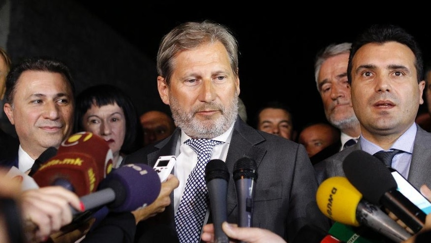 European Neighborhood Policy & Enlargement Negotiations commissioner Johannes Hahn, center, talks to the media in presence of Macedonian Prime Minister and leader of the VMRO-DPMNE conservative party Nikola Gruevski, left, leader of Macedonian opposition Social Democrats Zoran Zaev, right and leader of the Democratic Party of the Albanians Menduh Thaci, second from right, after their talks in Skopje, Macedonia, early Wednesday, July 15, 2015.  (AP Photo/Boris Grdanoski)
