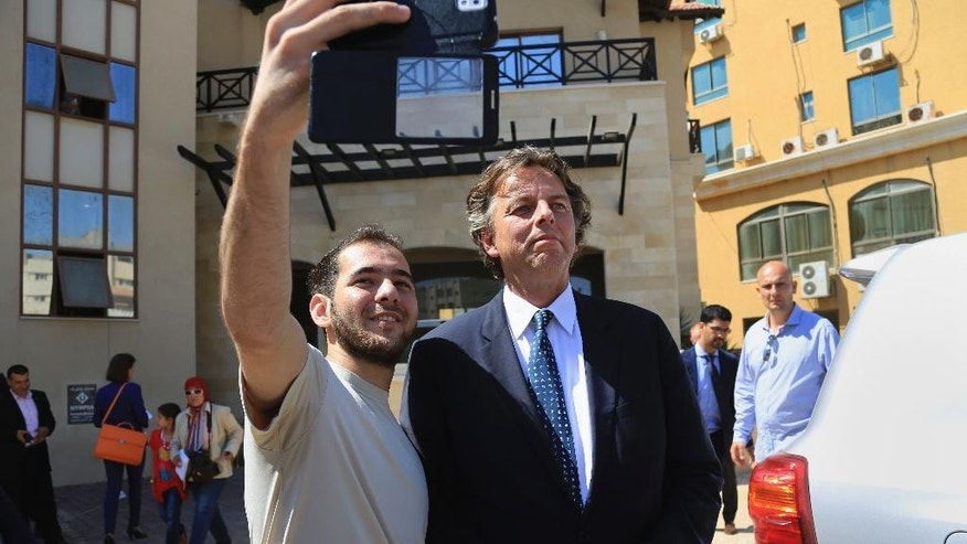 A Palestinian man takes a selfie with Dutch Foreign Minister Bert Koenders in front of Roots Hotel in Gaza City, in the northern Gaza Strip, Wednesday, July 15, 2015. Koenders, visited the Kerem Shalom Crossing in southern Israel, which borders Gaza, to inaugurate a new security scanning system. The machine was donated by the Netherlands, and aims to increase the number of trucks crossing into Gaza from Israel. (AP Photo/Adel Hana)