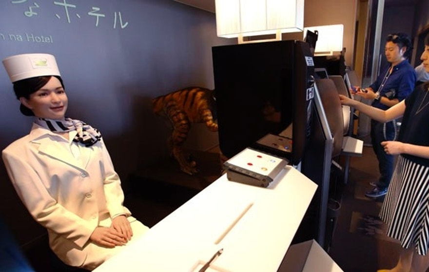 "A receptionist robot, left, greets a hotel employee, right, demonstrating how to check in for the media at the new hotel, aptly called Henn na Hotel or Weird Hotel, in Sasebo, southwestern Japan, Wednesday, July 15, 2015. From the receptionist that does the check-in and check-out to the porter that's a stand-on-wheels taking luggage up to the room, the hotel, that is run as part of Huis Ten Bosch amusement park, is ""manned"" almost totally by robots to save labor costs. (AP Photo/Shizuo Kambayashi)"