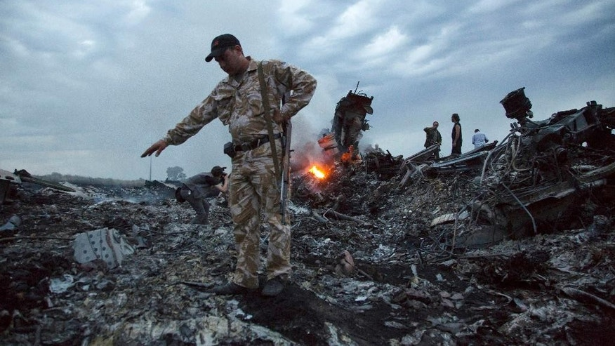 FILE - In this July 17, 2014. file photo, people walk amongst the debris at the crash site of a passenger plane near the village of Grabovo, Ukraine. For many families of the 298 people killed when Malaysia Airlines Flight 17 was brought down July 17, 2014 over eastern Ukraine, uncertainty and agonizing waiting is still woven into the fabric of their lives a year later. (AP Photo/Dmitry Lovetsky, File)