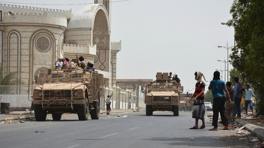 People watch fighters against Shiite rebels as they ride military vehicles on a street in the port city of Aden, Yemen, Tuesday, July 14, 2015. Yemeni forces battling the Shiite rebel known as Houthis in the country's south said they took control on Tuesday of the airport in the strategic port city of Aden, driving the rebels there into a part of the city jutting out into the sea. (AP Photo/Abo Muhammed)