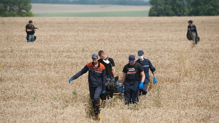 FOR STORY UKRAINE MH17 WHERE THINGS STAND - FILE - In this Saturday, July 19, 2014 file photo emergency workers carry the body of a victim at the crash site of a Malaysia Airlines jet near the village of Hrabove, eastern Ukraine.  A year since a Malaysia Airlines Boeing 777 was blown out of the sky over war-ravaged eastern Ukraine, killing 298 people, there has been little definitive progress in determining what brought down Flight MH17.  (AP Photo/Evgeniy Maloletka, file)