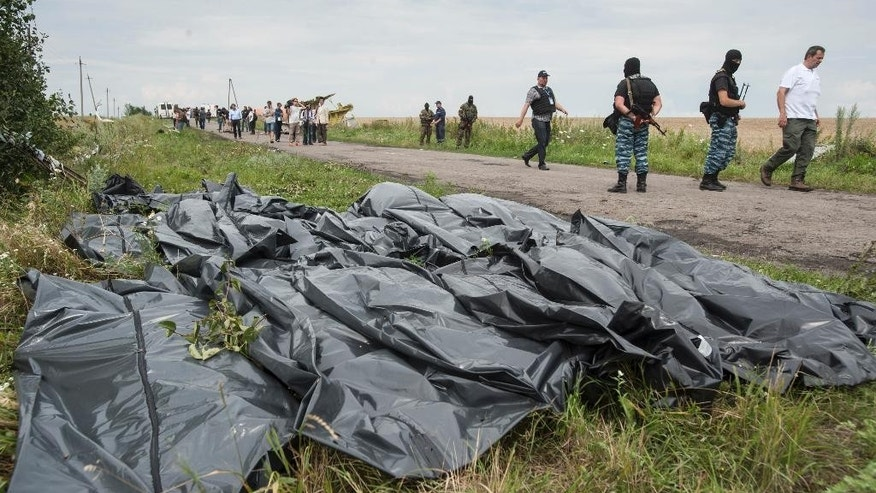 FOR STORY UKRAINE MH17 WHERE THINGS STAND  - FILE - In this Saturday, July 19, 2014 file photo pro-Russian fighters walk on a road with victims' bodies lying in bags by the side at the crash site of a Malaysia Airlines jet near the village of Hrabove, eastern Ukraine. A year since a Malaysia Airlines Boeing 777 was blown out of the sky over war-ravaged eastern Ukraine, killing 298 people, there has been little definitive progress in determining what brought down Flight MH17.  (AP Photo/Evgeniy Maloletka, file)