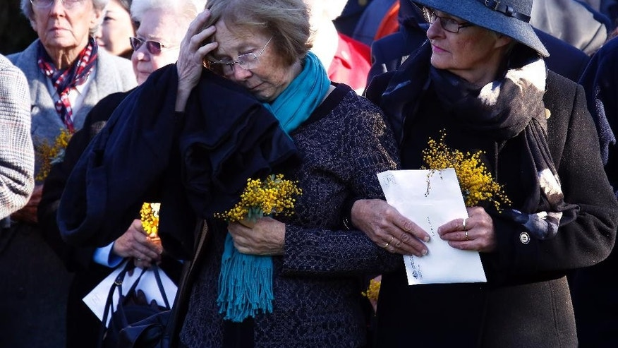 Relatives of the Australian victims of Malaysia Airlines jet MH17 attend a service for the unveiling of a memorial outside Parliament House in Canberra, Australia, Friday, July 17, 2015.  Tearful relatives of several Australians who were flying on the Malaysian jetliner that was shot down over eastern Ukraine a year ago gathered for a memorial service Friday that included the unveiling of a plaque set in soil from the place where they died.(AP Photo/David Gray, Pool)
