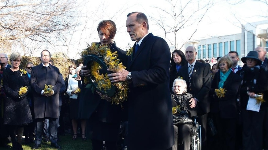 Australian Prime Minister Tony Abbott center, and his wife Margaret prepare to lay a wreath for the Australian victims of Malaysia Airlines jet MH17 at a ceremony unveiling a memorial outside Parliament House in Canberra, Australia, Friday, July 17, 2015. Tearful relatives of several Australians who were flying on the Malaysian jetliner that was shot down over eastern Ukraine a year ago gathered for a memorial service Friday that included the unveiling of a plaque set in soil from the place where they died.(AP Photo/David Gray, Pool)
