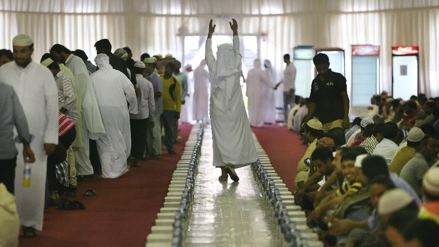 In this photo taken Tuesday, June 30, 2015, an Emirati man invites people to join iftar at the end of the fasting day inside a tent at the Sheikh Zayed Grand Mosque in Abu Dhabi, United Arab Emirates. Efforts by Muslims to modernize Islam are nothing new. For centuries, Muslim theologians, philosophers, poets, jurists and scientists advanced not only their understanding of Islam but the world. (AP Photo/Kamran Jebreili)