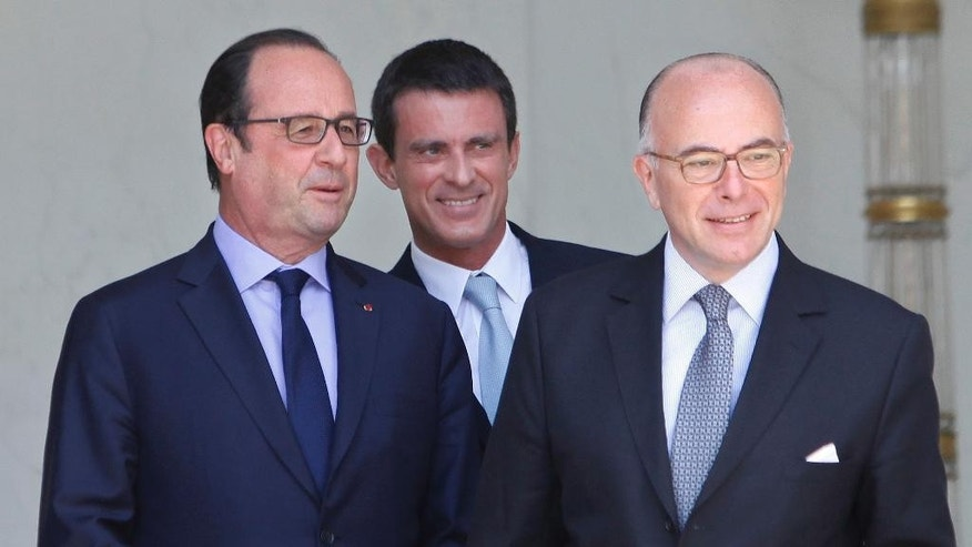 France's President Francois Hollande, left, talks with Prime Minister Manuel Valls, center, and Interior Minister Bernard Cazeneuve, right, in the lobby of the Elysee Palace after the weekly cabinet meeting in Paris, France, Wednesday, July 15, 2015. (AP Photo/Thibault Camus)