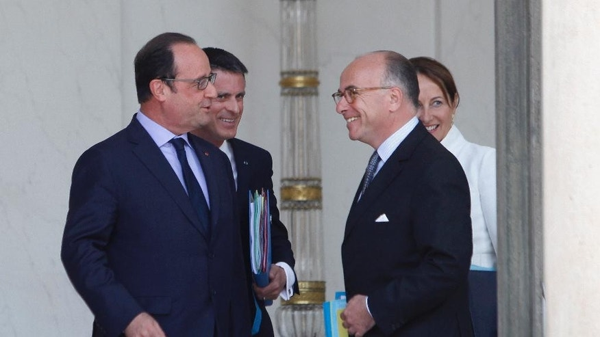 France's President Francois Hollande, left, talks with Prime Minister Manuel Valls, second left, Interior Minister Bernard Cazeneuve, center right, and Environment Minister Segolene Royal, right, in the lobby of the Elysee Palace after the weekly cabinet meeting in Paris, France, Wednesday, July 15, 2015. (AP Photo/Thibault Camus)