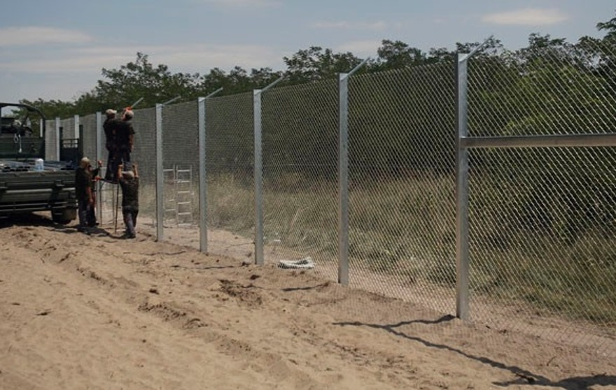 Hungarian soldiers build a fence near Morahalom, Hungary, Thursday, July 16, 2015. A fence on Hungary's border with Serbia to stem the flow of migrants and refugees will be complete by Nov. 30, the Hungarian defense minister said Thursday. Csaba Hende said that 900 people would work to install the fence, which is planned to be 4 meters (13 feet) high along the 175-kilometer (109-mile) border between Hungary and Serbia.  (AP Photo/Darko Vojinovic)