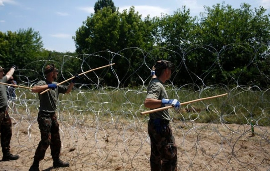 Hungarian soldiers place a barbed wire fence near Morahalom, Hungary, Thursday, July 16, 2015, as work continues to build a border fence between Hungary and Serbia to stem the flow of migrants. Defense Minister Csaba Hende said Thursday that 900 people would work simultaneously on 10-12 sections of the fence which is planned to be 4 meters (13 feet) high along the 175-kilometer (109-mile) border between Hungary and Serbia. (AP Photo/Darko Vojinovic)