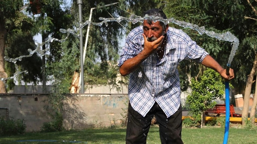 An Iraqi man cools himself with water in central Baghdad, Iraq, Thursday, July 16, 2015. The government declared Thursday an official holiday due to scorching temperatures. Health authorities have warned people not to expose themselves to the sun, with hospitals already receiving an overwhelming number of heat-related cases. (AP Photo/Karim Kadim)