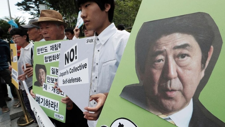 """South Korean protesters stage a rally to protest against Japanese parliament's possible approval of the controversial security legislation in front of the Japanese embassy in Seoul, South Korea, Thursday, July 16, 2015.  A Japanese parliamentary committee on Wednesday approved legislation that would expand the role of Japan's military after Prime Minister Shinzo Abe's ruling bloc forced the vote in the face of protests from some lawmakers and citizens. Then letters at banners read """"No! Japan's Collective Self-defense."""" (AP Photo/Ahn Young-joon)"""