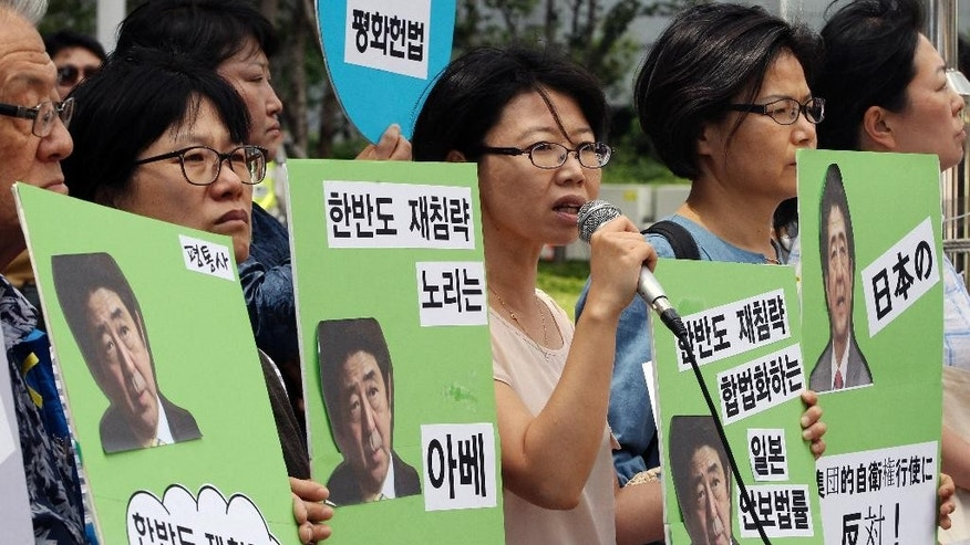 """South Korean protester stage a rally to protest against Japanese parliament's possible approval of the controversial security legislation in front of the Japanese embassy in Seoul, South Korea, Thursday, July 16, 2015.  A Japanese parliamentary committee on Wednesday approved legislation that would expand the role of Japan's military after Prime Minister Shinzo Abe's ruling bloc forced the vote in the face of protests from some lawmakers and citizens. Then letters at banners read """"No! Japan's Collective Self-defense and We denounce Abe's government."""" (AP Photo/Ahn Young-joon)"""