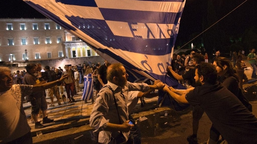 Protesters scuffle with each other to tear down a Greek flag with a writing reading ''Greece we love you'' during a rally outside the Greek Parliament in Athens, Wednesday, July 15, 2015. Greece's prime minister was fighting to keep his government intact in the face of outrage over an austerity bill that parliament must pass Wednesday night if the country is to start negotiations on a new bailout and avoid financial collapse. (AP Photo/Emilio Morenatti)