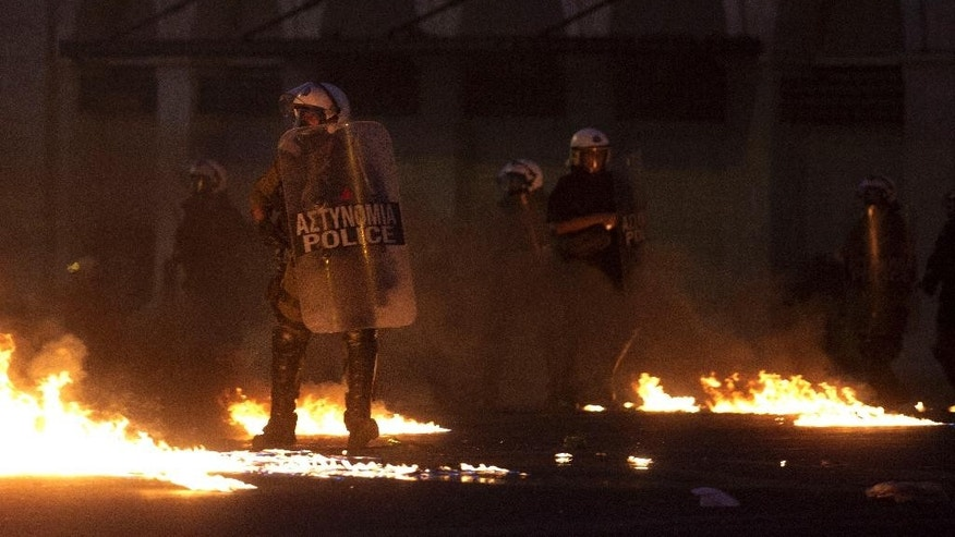 Riot police try to avoid petrol bombs thrown by anti-austerity protesters in Athens, Wednesday, July 15, 2015. Greece has a tentative rescue deal, but relief that it is not falling out of the euro is unlikely to last long: its economy has taken a huge hit. Months of political brinkmanship, uncertainty and bank closures have hurt companies and brought everyday business to a standstill. (AP Photo/Petros Giannakouris)