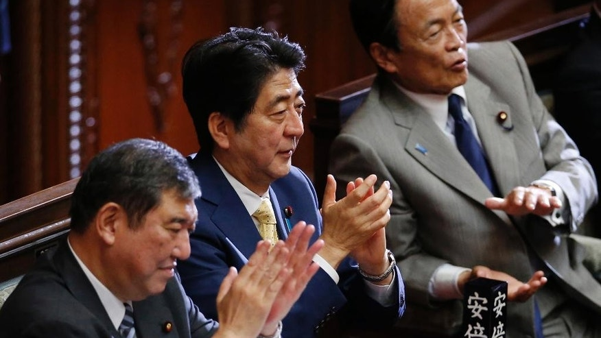 Japanese Prime Minister Shinzo Abe, center, claps hands during a plenary session at the lower house in Tokyo, Thursday, July 16, 2015.  Japan's lower house of parliament on Thursday approved legislation that would allow an expanded role for the nation's military in a vote boycotted by the opposition. Finance Minister Taro Aso is at right.  Shigeru Ishiba, the minister for Vitalizing Local Economy in Japan is seen at left.(AP Photo/Shuji Kajiyama)