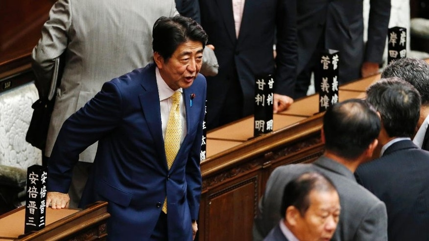 Japanese Prime Minister Shinzo Abe, left, greets his ruling party lawmakers after a plenary session at the lower house in Tokyo, Thursday, July 16, 2015.  Japan's lower house of parliament on Thursday approved legislation that would allow an expanded role for the nation's military in a vote boycotted by the opposition. (AP Photo/Shuji Kajiyama)