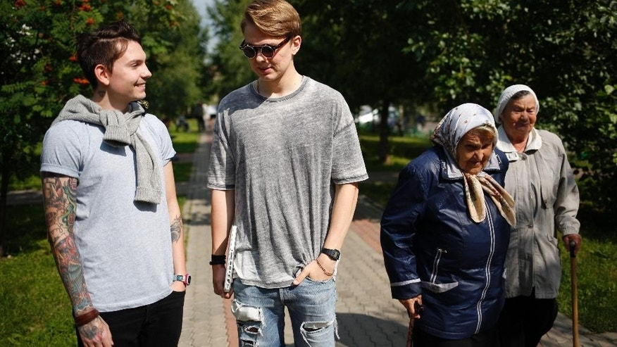 Video bloggers Artyom Frantsuzov, second left, and Yevgeny Babenko, left, prepare for an interview with the Associated Press in Moscow, Russia, Wednesday, July 15, 2015. Frantsuzov and Babenko, neither of whom are gay, made a video that depicted them as a couple, filmed by a hidden camera in public places, as a 'social experiment' to demonstrate how Russians react to homosexuality in public. (AP Photo/Alexander Zemlianichenko)