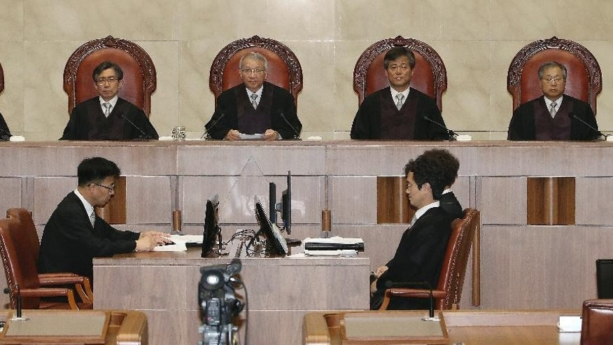 South Korean Supreme Court Chief Justice Yang Sung-tae, top center, sits with other judges before the judgment at the Supreme Court in Seoul, South Korea, Thursday, July 16, 2015. South Korea's Supreme Court has ordered a new trial for a former spy chief convicted of directing an online campaign to smear a main opposition candidate in the 2012 presidential election. (Lim Hun-jung/Yonhap via AP) KOREA OUT