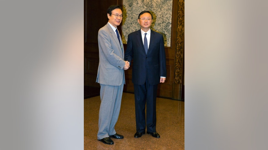 Japanese National Security Adviser Shotaro Yachi, left, shakes hands with Chinese State Councilor Yang Jiechi during a meeting at the Diaoyutai State guesthouse in Beijing, Thursday, July 16, 2015. (AP Photo/Ng Han Guan, Pool)