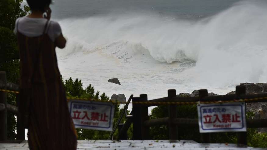 In this July 16, 2015 photo, waves crash against Katsurahama in Kochi on the island of Shikoku, western Japan, as a strong tropical storm sweeps across western Japan. Tropical Storm Nangka caused serious flooding Friday morning, July 17,  and disrupted air and train travel as it crossed the island of Shikoku and the main Japanese island of Honshu. (Kyodo News via AP) JAPAN OUT, MANDATORY CREDIT