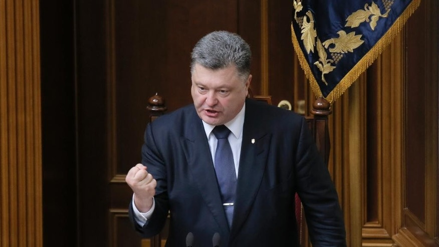 "Ukrainian President Petro Poroshenko gestures as he speaks to lawmakers during a parliament session in Kiev, Ukraine, Thursday, July 16, 2015. Ukraine's parliament, on Thursday sent to the Constitutional Court draft amendments to the country's Constitution concerning decentralization. A total of 288 lawmakers, 62 more than the minimum required voted in favor of the decision. The Constitution is added by a provision that ""the peculiarities of local self-government in certain areas of the Donetsk and Lugansk regions are defined by a separate law."" (AP Photo/Efrem Lukatsky)"
