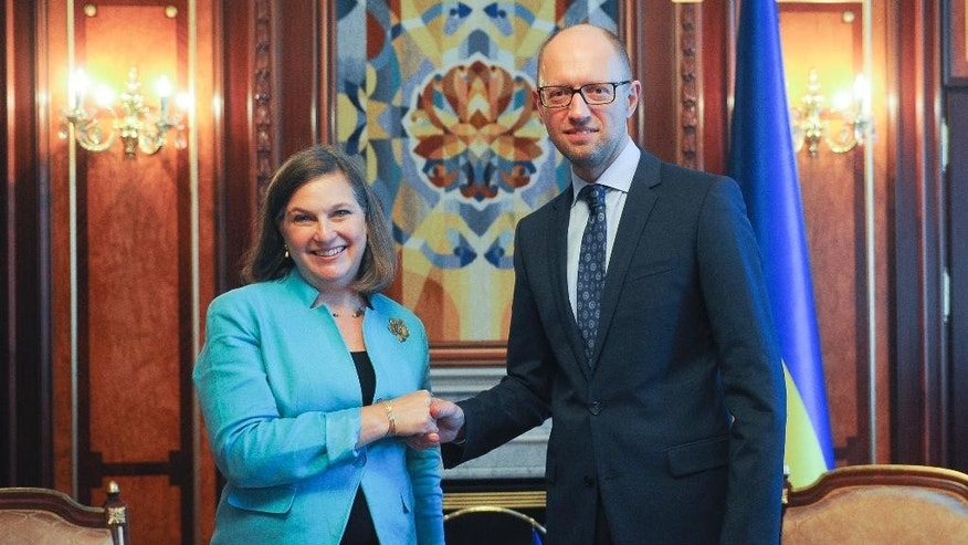 U.S. Assistant Secretary of State Victoria Nuland, left, and Ukrainian Prime Minister Arseniy Yatsenyuk shake hands during their meeting in Kiev, Ukraine, Thursday, July 16, 2015.  (AP Photo/Andrew Kravchenko, Pool)