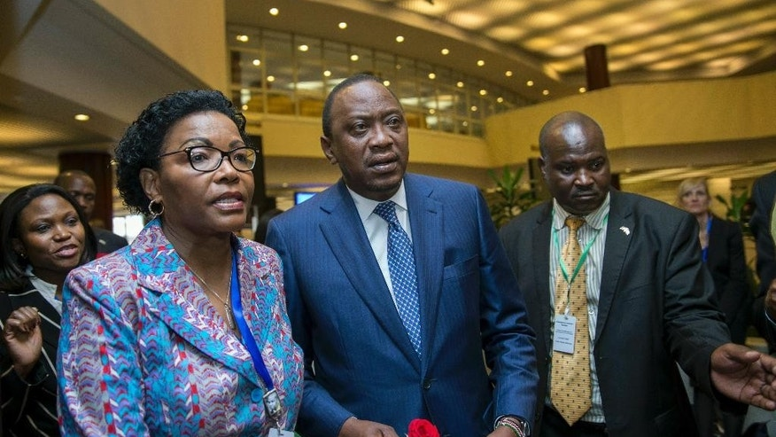 """Kenya's President Uhuru Kenyatta, center, arrives for the opening of The Third International Conference on Financing for Development, held in Addis Ababa, Ethiopia, Monday, July 13, 2015. According to the organizers, the conference which runs from July 13-16 is intended to gather world leaders to """"launch a renewed and strengthened global partnership for financing people-centered sustainable development"""". (AP Photo/Mulugeta Ayene)"""