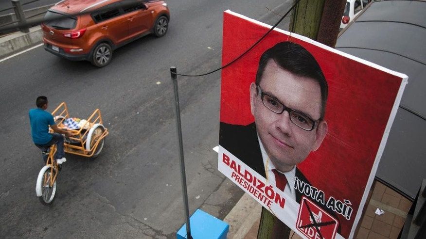 A campaign poster promoting presidential candidate Manuel Baldizon of the Democratic Freedom Revival Party, hangs from a utility pole, in Santa Catarina Pinula, Guatemala, Thursday, July 16, 2015. A report of the United Nations International Commission Against Impunity targeting corruption in Guatemala says a percent of the money fueling its politics comes from criminal organizations, primarily drug traffickers. The report was released one day after the same commission and Guatemalan prosecutors petitioned to have Baldizon's running mate stripped of his immunity for allegedly laundering funds that were later used to finance political activities.  (AP Photo/Luis Soto)