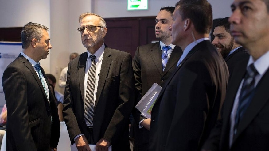 Flanked by staff and security detail,  Ivan Velasquez, commissioner of the United Nations International Commission Against Impunity, second left, before presenting a report on Guatemala's campaign financing, in Guatemala City, Thursday, July 16, 2015. The commission concluded that the country's elections are rife with illegal money and corruption is the glue holding the system together. Political parties consistently spend far more money than they report taking in and several regularly exceed spending limits without consequence. (AP Photo/Luis Soto)