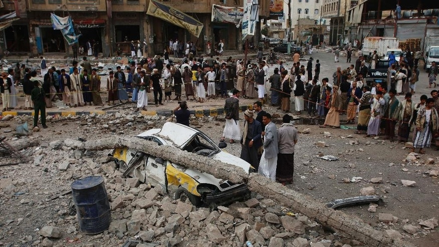 People stand near a vehicle destroyed following airstrikes by the Saudi-led coalition in Sanaa, Yemen, Tuesday, July 14, 2015. The coalition has been targeting the Iran-allied Houthis since March in a bid to stop their power grab across the country. Yemeni forces battling the Shiite rebels in the country's south said they took control on Tuesday of the airport in the strategic port city of Aden. (AP Photo/Hani Mohammed)