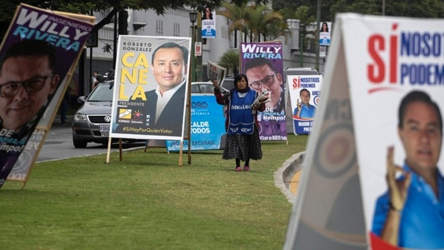 A newspaper vendor walks through a row of A-frame signs promoting presidential and mayoral candidates in Guatemala City, Thursday, July 16, 2015. A report of the United Nations International Commission Against Impunity targeting corruption in Guatemala says a percent of the money fueling its politics comes from criminal organizations, primarily drug traffickers. The report was released one day after the same commission and Guatemalan prosecutors petitioned to have a candidate for vice president stripped of his immunity for allegedly laundering funds that were later used to finance political activities. (AP Photo/Luis Soto)