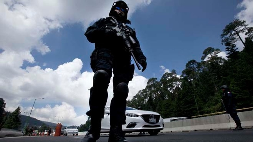 "Federal Police patrol a checkpoint west of Mexico City, Thursday, July 16, 2015. A widespread manhunt that included highway checkpoints, stepped up border security and closure of an international airport failed to turn up any trace of drug lord Joaquin ""El Chapo"" Guzman after he escaped through an underground tunnel in his prison cell. (AP Photo/Marco Ugarte)"
