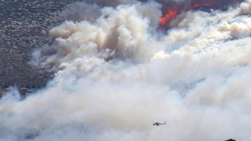 An helicopter flies over a fire in the eastern suburbs of Athens on Friday, July 17, 2015. The brush fire broke out on the outskirts of the Greek capital, burning across a hillside and blanketing parts of Athens in thick smoke. The blaze moved fast, fanned by strong winds and devouring parts of a verdant hillside popular with day-trippers. (AP Photo/Thanassis Stavrakis)