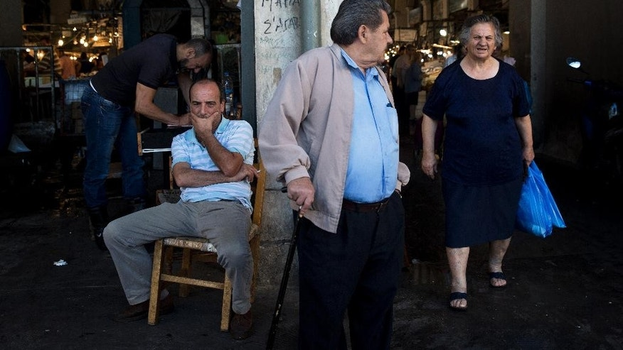 An elderly couple leaves the central fish market in Athens, on Friday, July 17, 2015. Greece on Thursday won vital pledges of support from bailout lenders needed to keep its economy from collapsing, but officials in Athens said the painful austerity measures demanded in return were likely to force an election within months. (AP Photo/Petros Giannakouris)