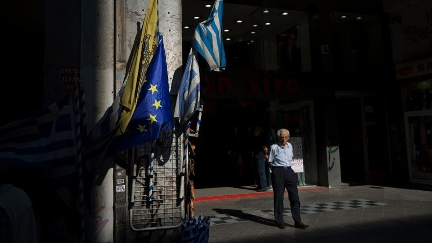 A man stands next to a shop selling Greek and European Union flags in central Athens, Thursday, July 16, 2015. Greece's troubled left-wing government is seeking urgent relief from European lenders on Thursday, after it pushed a harsh austerity package thought parliament, triggering a revolt in the ruling party and violent demonstrations in central Athens. (AP Photo/Emilio Morenatti)