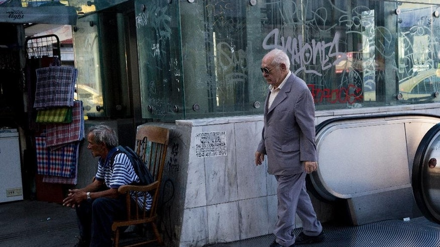 A elderly man exits a metro station in central Athens, on Friday, July 17, 2015. Greece on Thursday won vital pledges of support from bailout lenders needed to keep its economy from collapsing, but officials in Athens said the painful austerity measures demanded in return were likely to force an election within months.(AP Photo/Petros Giannakouris)