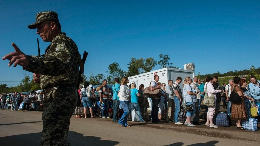 A Ukrainian army officer tries to handle residents of the Donetsk and Luhansk regions as they wait to cross a Ukrainian government forces' checkpoint at the road from Horlivka to Artemivsk to leave the territory controlled by Russia-backed separatists for Ukrainian territory near Artemivsk, Donetsk region,  eastern Ukraine, Friday, July 17, 2015. (AP Photo/Evgeniy Maloletka)