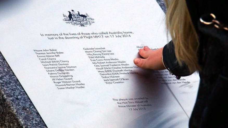 A relative of an Australian victim of Malaysia Airlines flight MH17 touches a memorial that was unveiled outside Parliament House in Canberra, Australia, Friday, July 17, 2015. Tearful relatives of several Australians who were flying on the Malaysian jetliner that was shot down over eastern Ukraine a year ago gathered for a memorial service Friday that included the unveiling of a plaque set in soil from the place where they died.(AP Photo/David Gray, Pool)