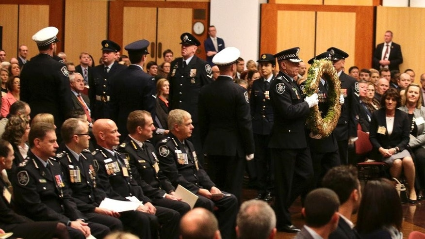 Australian Federal Police officers carry a wreath to commemorate Australians that lost their lives in the MH17 disaster during a memorial service for the one year anniversary at Parliament House in Canberra, Australia, Friday, July 17, 2015. Thirty-eight Australian citizens and permanent residents among the 298 people on Malaysia Airlines Flight 17, which was heading from Amsterdam to Kuala Lumpur on July 17, 2014, when it was shot down. Everyone on board was killed.(AP Photo/Rob Griffith, Pool)