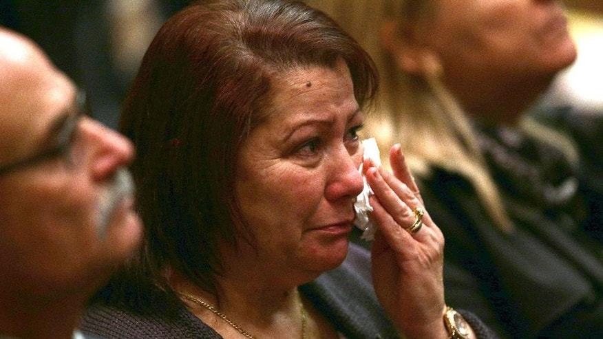 A Rizk family member sheds a tear during a memorial service for the one year anniversary for Australians that lost their lives in the MH17 disaster at Parliament House in Canberra, Australia, Friday, July 17, 2015. Thirty-eight Australian citizens and permanent residents among the 298 people on Malaysia Airlines Flight 17, which was heading from Amsterdam to Kuala Lumpur on July 17, 2014, when it was shot down. Everyone on board was killed.(AP Photo/Rob Griffith, Pool)