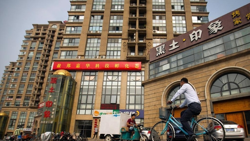 In this Friday, July 17, 2015 photo, a delivery cart and cyclist ride past a building housing the Fengrui law firm in Beijing. Since late May, police across China have detained and called in at least 215 rights lawyers and social activists, including many of Fengrui's lawyers. State propaganda has kicked into high gear to denounce them as rabble-rousers, criminal gangs, and profit-seeking opportunists. (AP Photo/Mark Schiefelbein, File)