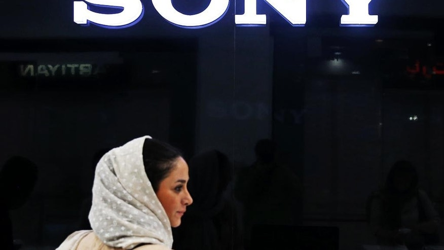 In this picture taken on Friday, July 17, 2015, an Iranian woman walks past a Sony dealer at a shopping center in downtown Tehran, Iran. While it will likely be months before sanctions on Iran ease, business and political leaders are wasting no time in trying to tap into a large and what they hope will be a lucrative Iranian market. Ads for European cars and luxury goods are starting to reappear in Tehran. American firms, though, have to be much more cautious. Deal or no deal, U.S. sanctions not related to the nuclear program will still be in place and bar most American companies from doing business with Iran. (AP Photo/Ebrahim Noroozi)