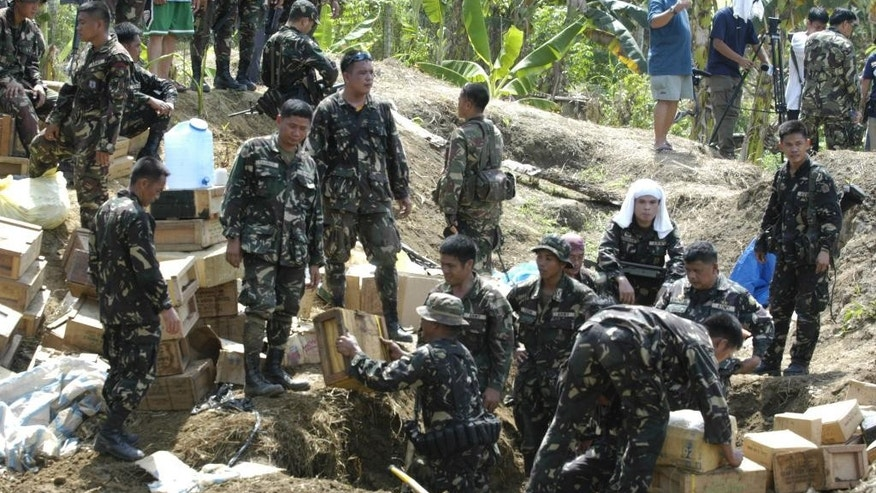 FILE - In this Saturday, Dec. 12, 2009, file photo, soldiers dig out thousands of rounds of M16 and M14 ammunition buried in the pit outside the farm of Maguindanao Gov. Andal Ampatuan Sr., in Shariff Aguak township, Maguindanao province in southern Philippines. The lawyer for Ampatuan, one of the main suspects on trial for the 2009 massacre of 58 people in the southern Philippines, says his client died overnight on Friday, July 17, 2015, in a government hospital. Ampatuan was brought to the National Kidney and Transplant Institute in early June and was diagnosed with liver cancer. (AP Photo/Froilan Gallardo, File)